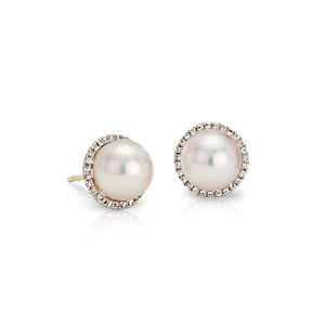 Akoya pearls are surrounded by a halo of round diamonds set in 14k yellow gold.