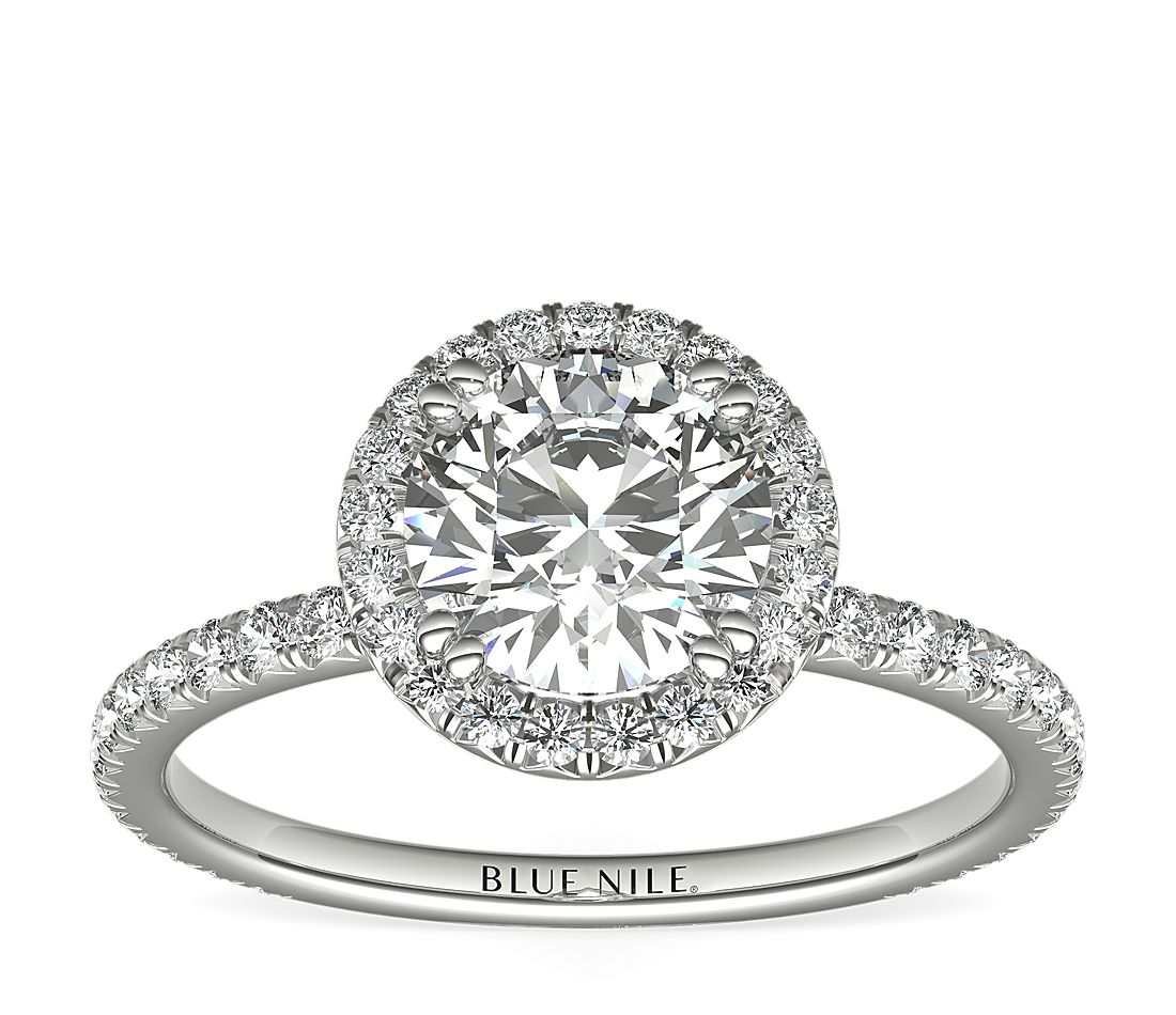An engagement ring with a 1-carat round center diamond surrounded by french pavé set diamonds.