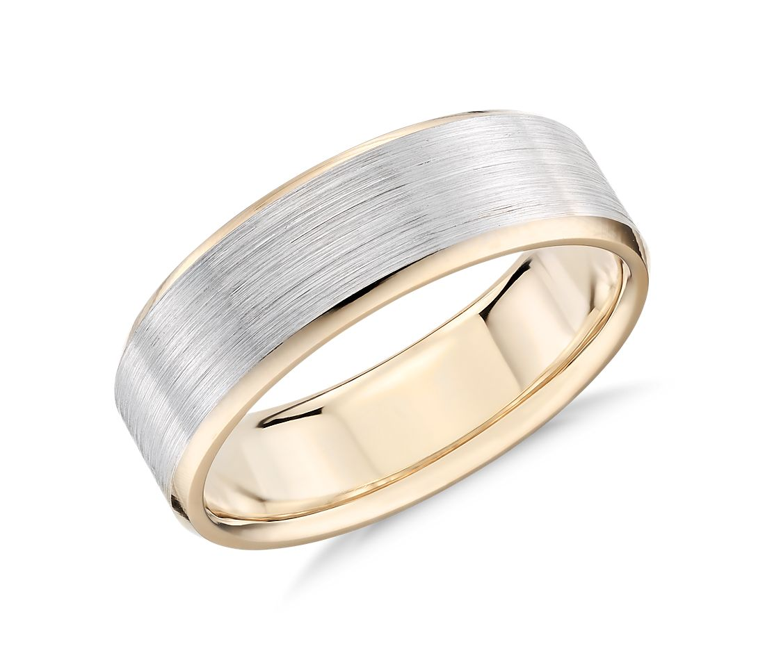 A wedding band that has a white inlay band with a yellow gold outside.