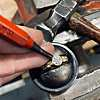 An artisan at work on Love's beautiful bezel-set diamond ring.