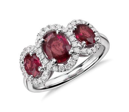 Anillo de tres rubíes ovalados y halo de diamantes en oro blanco de 18 k (7x5mm)