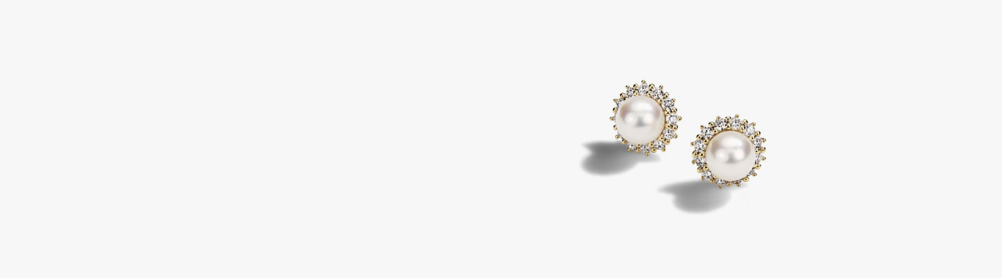 Freshwater cultured pearls surrounded by round diamonds and framed in 14k yellow gold.