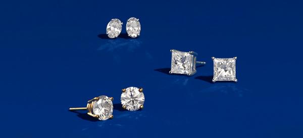 四对形状独特的钻石耳钉,镶嵌于蓝绿色背景之上。