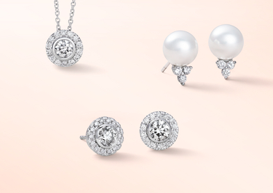 A diamond halo pendant, diamond halo stud earrings, and pearl stud earrings