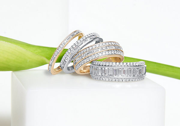 Cuatro alianzas de bodas con diamantes ZAC Zac Posen dispuestas una junto a la otra frente al tallo de una flor