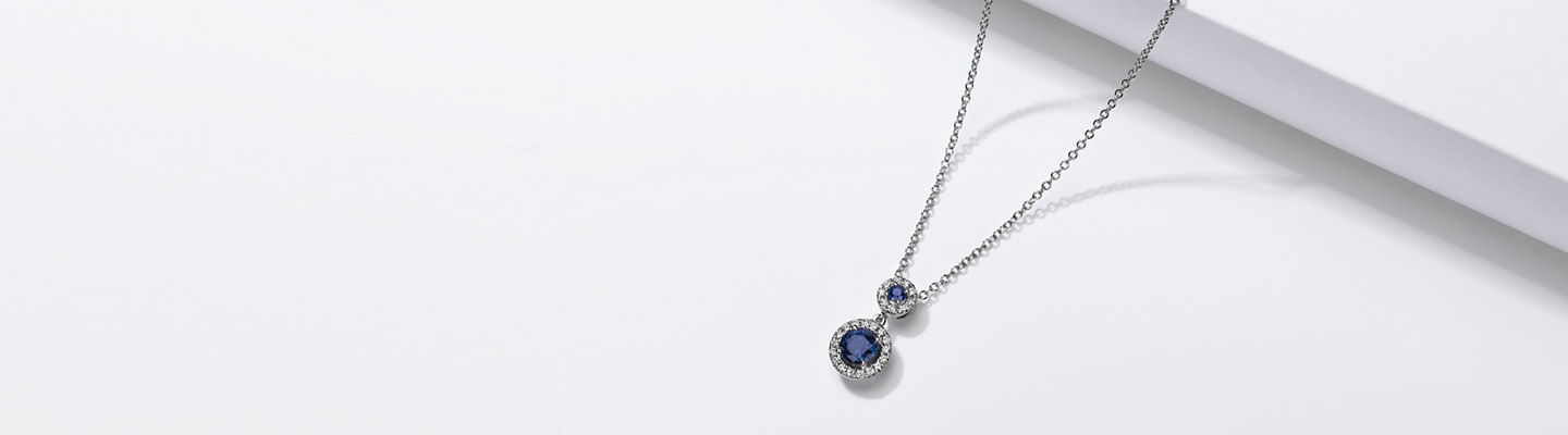 14k white gold pendant featuring two sapphires surrounded by diamond halos.