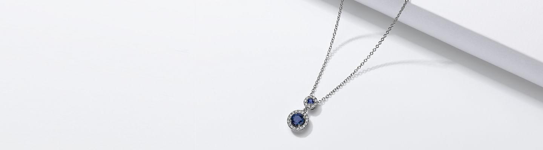 Pendentif en or blanc 14carats orné de deux saphirs entourés par des halos de diamants.