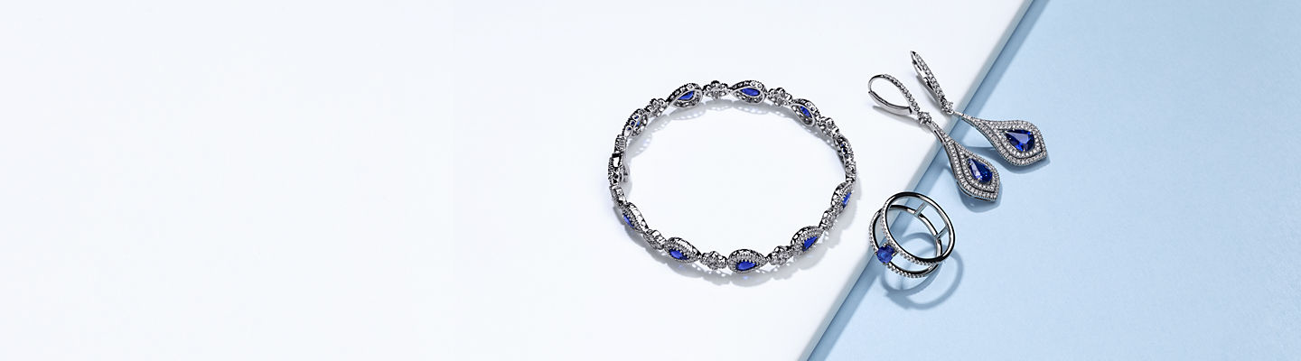 A bracelet, ring, and pair of earrings featuring sapphires surrounded by pavé-set diamonds.