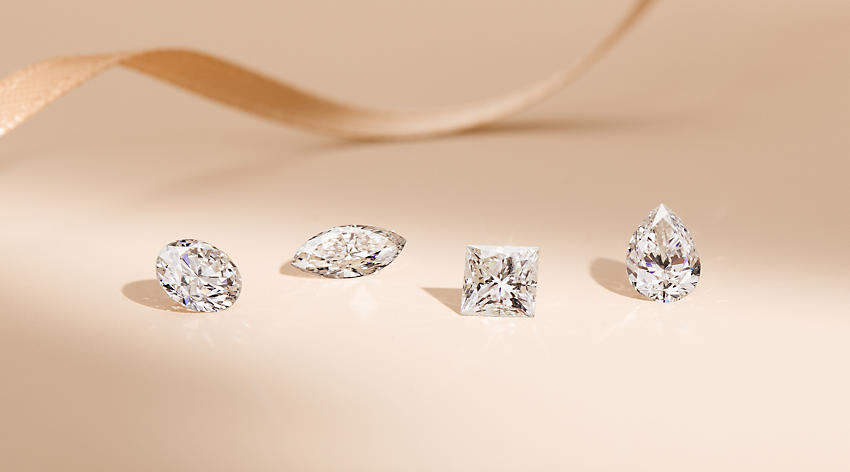 A group of four loose diamonds featuring round, marquise, cushion and pear shapes