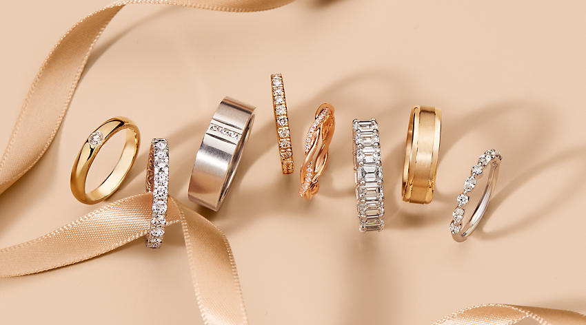 A group of wedding rings for women and men featuring diverse styles with diamonds and high-quality precious metals