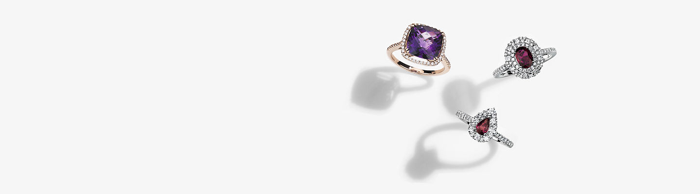 Two ruby gemstone rings set in diamond halos, and a rose gold ring set with an amethyst in a diamond halo.