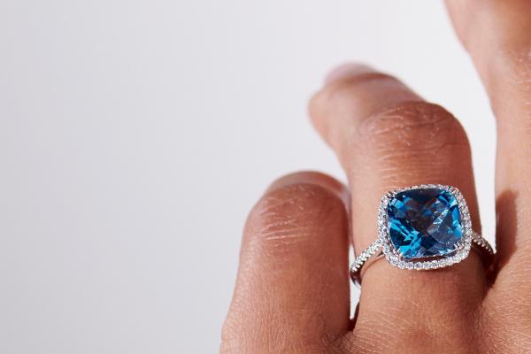 佩戴藍色托帕石雞尾酒戒指的女性手指的近照。