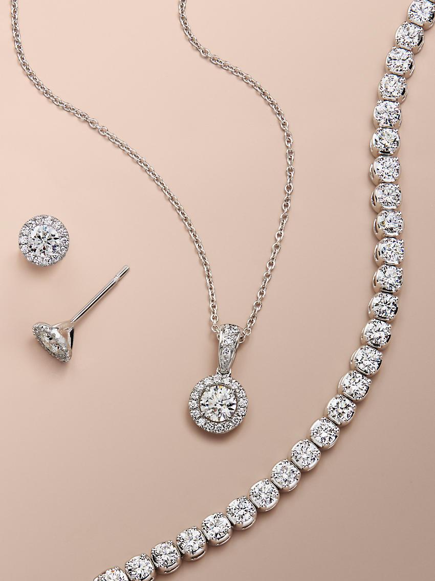 A diamond pendant, tennis bracelet and stud earrings