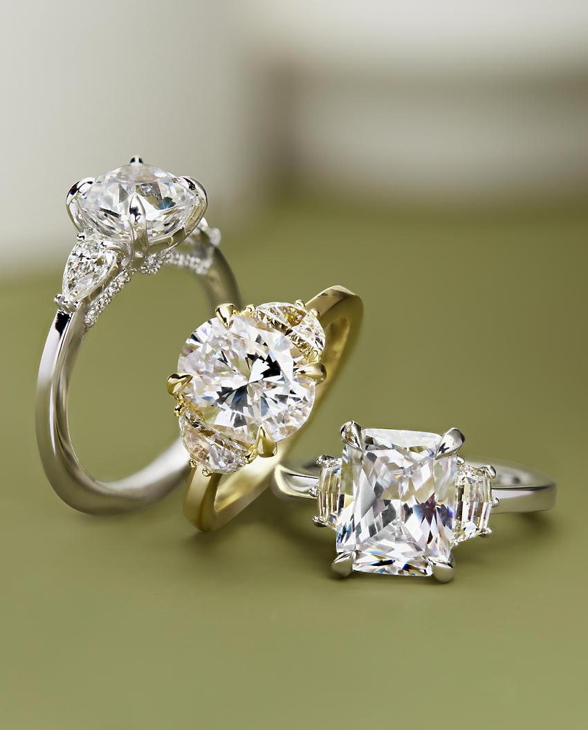 An assortment of three-stone diamond engagement rings