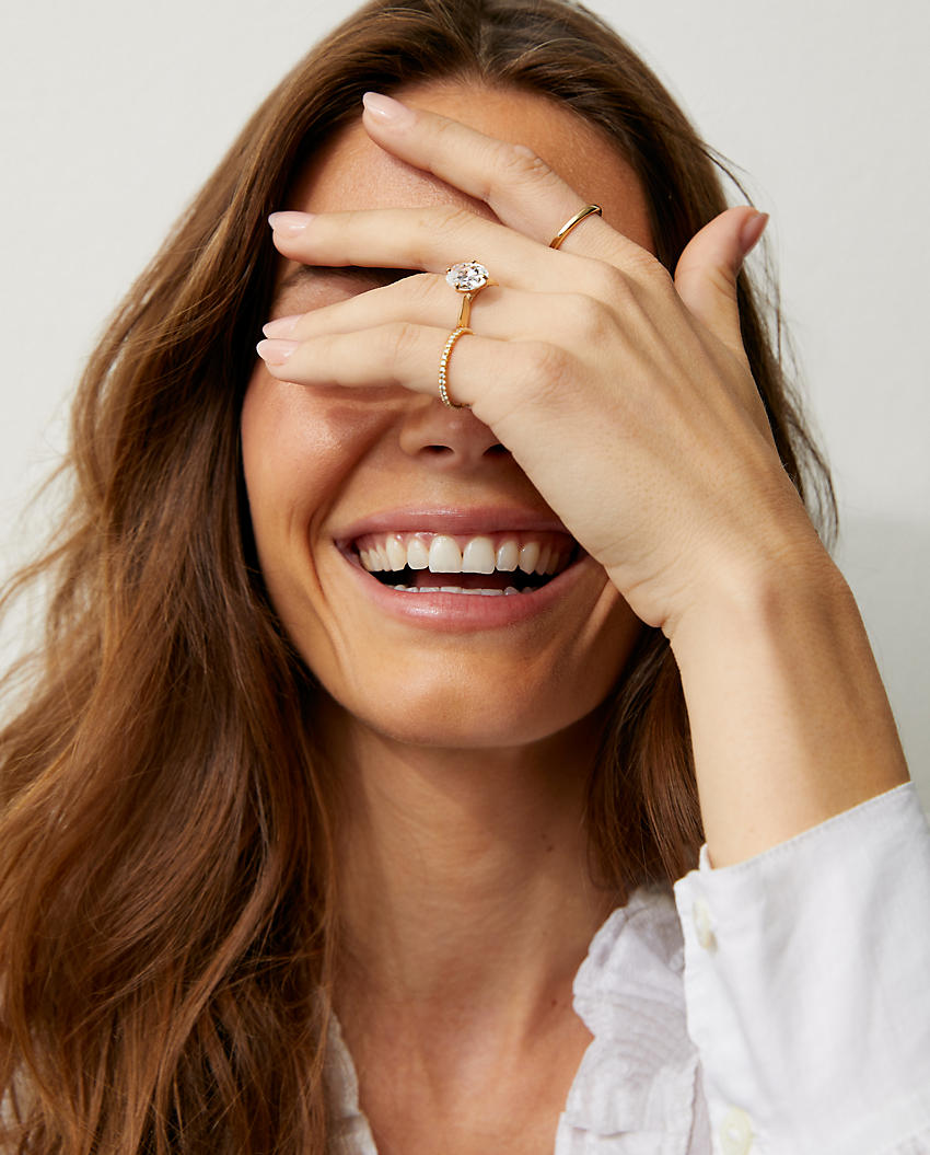 Woman wearing an engagement ring and two bands with her hand over her face
