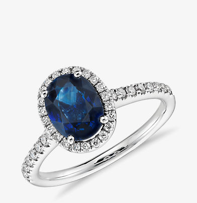 Micropavé diamond halo ring featuring an oval blue sapphire centre stone in 14k white gold.