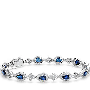Bracelet consisting of blue sapphires accented with halos of pavé-set diamonds in 18k white gold.