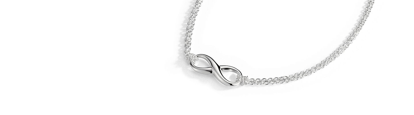 An infinity symbol hanging from a cable chain in sterling silver.