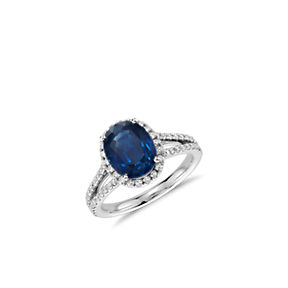 A split shank ring set with an oval sapphire gemstone surrounded by a halo of diamonds.