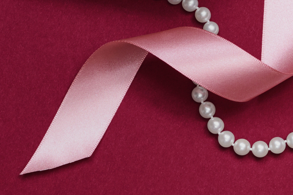A pearl strand necklace and pink ribbon intertwined.