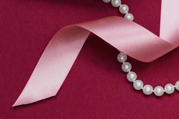 珍珠鏈串項鍊與粉紅色緞帶交織。