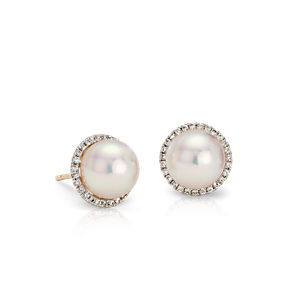 Pearl stud earrings surronded by a halo of round diamonds in 14k yellow gold.