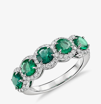 Ring made up of 5 round emeralds each sourounded by a diamond halo in 18k white gold.