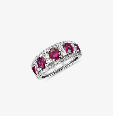 A wide gemstone and diamond ring with five oval rubies surrounded by diamonds.