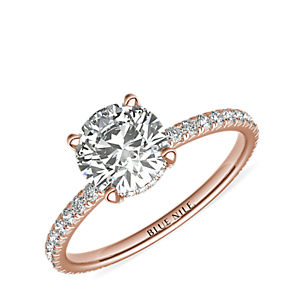 French pavé diamond engagement ring set with a round center stone.