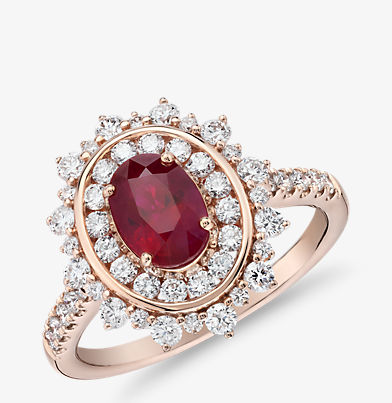 Double diamond halo ring with an oval ruby centre stone in 14k rose gold.