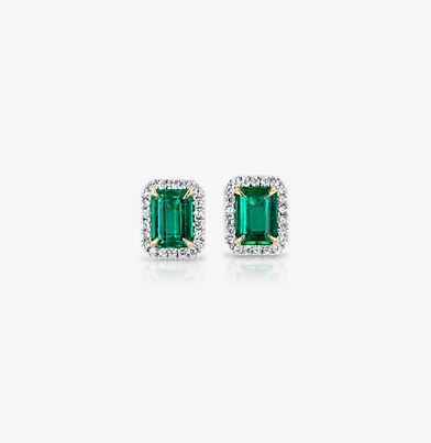 Large emerald earrings surrounded by diamond halos set in yellow gold studs.