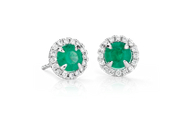 Emerald earrings surrounded by a halo of brilliant round diamonds in 18k white gold.