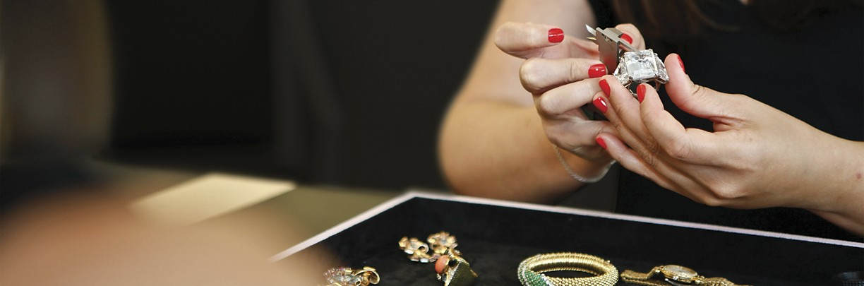 A woman inspecting a piece of jewelry.