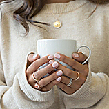 Woman holding a cup of coffee while wearing four rings.