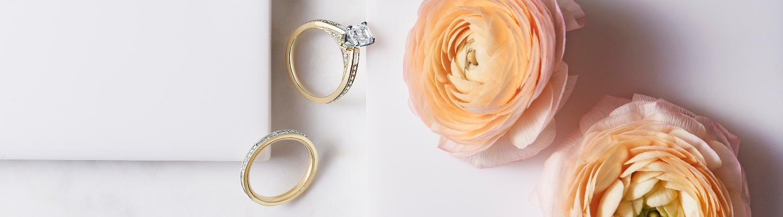 一枚 ZAC Zac Posen 单石订婚戒指,置于一枚钻石结婚戒指和一束桃红色的花朵旁边