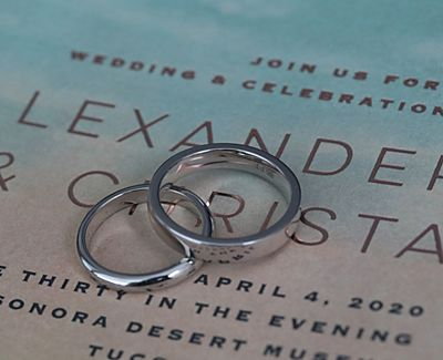 The couple's platinum wedding bands atop their wedding invitation.