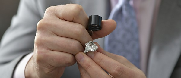 A man inspecting an engagement ring with a loop