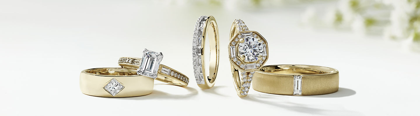 A ZAC Zac Posen solitaire engagement ring arranged next to a diamond wedding band and peach coloured flowers