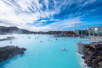 Relax in the geothermal waters under blue skies.