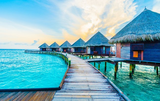 Floating huts over an azure ocean expanse.