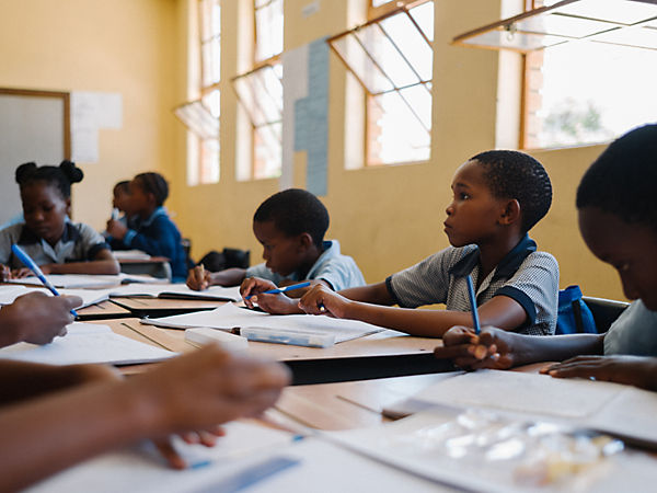 School children writing in notebooks at Mokobaxane Primary School, Orapa