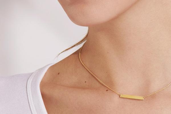 佩戴黃金長條項鍊的女人的近照。