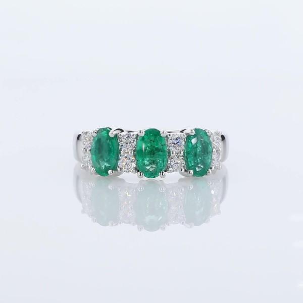 Anillo de tres piedras de esmeralda y diamante con halo en oro blanco de 14 k